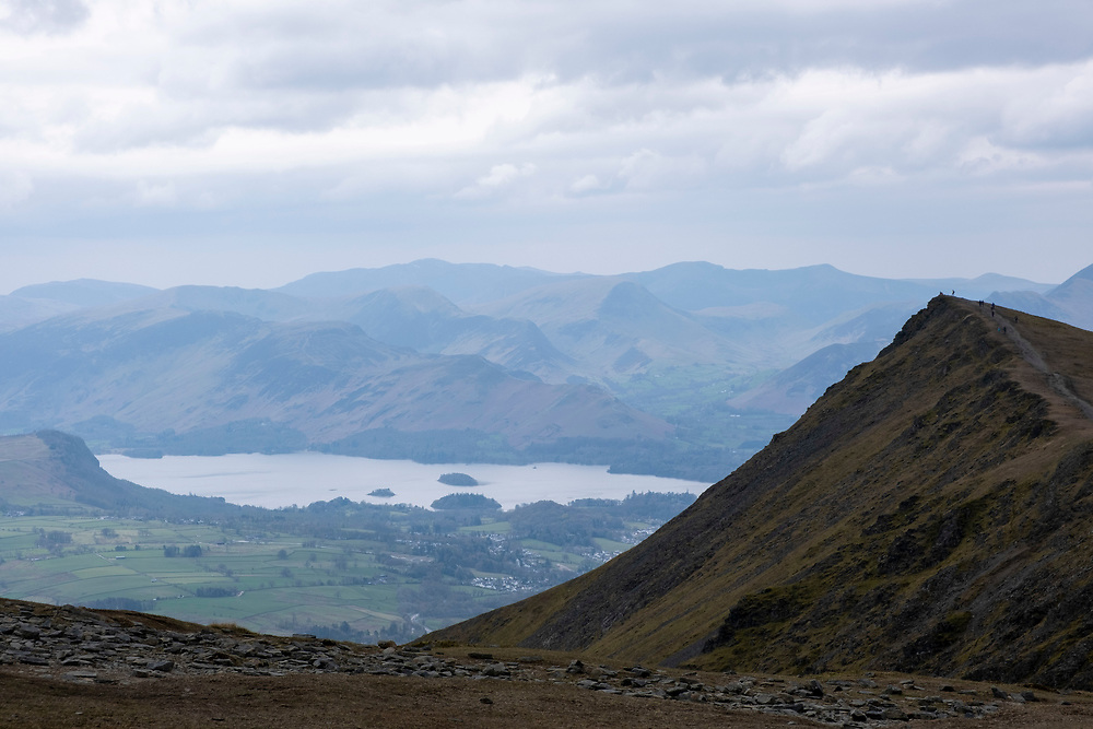 Hikers walk along the trail path to the peak of Blencathra Mountain, Lake Districts, Cumbria, UK. In the background is Derwentwater Lake flanked by hills and valleys of the Lake District National Park.  (photo by Andrew Aitchison / In pictures via Getty Images)