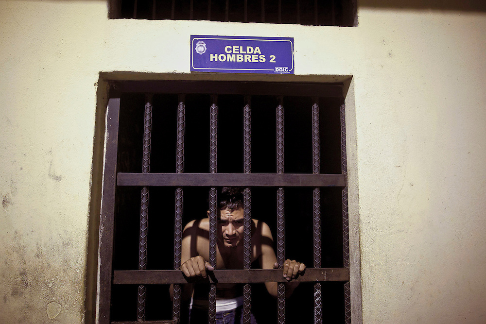 In this March 8, 2012 photo, a detainee peers through the jail bars at a police station in San Pedro Sula, Honduras. A wave of violence has made Honduras among the most dangerous places on Earth, with a homicide rate roughly 20 times that of the U.S. rate, according to a 2011 United Nations report.