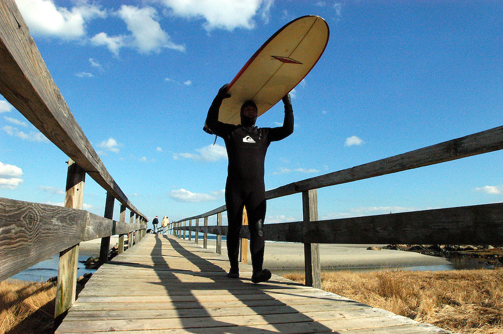 "Gloucester: Todd Bleckley of Malden carries his surf board on his head while crossing the footbridge at Good Harbor Beach Tuesday. Bleckley and his fiancee, Heidi O'Brien, both tested the waters but said the conditions were rougher than they expected so they were packing it in for the day. The trip wasn't a waste though, said Bleckley. ""A bad day surfing is better than no surfing at all."" .Photo by Mike Dean/Gloucester Daily Times Tuesday, February 19, 2008"