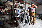 A female Nepalese worker of R.C rug factory in Narayanthan area of Kathmandu, Nepal. She is weighing a bundle of raw wool. The company export rugs and carpets to Europe the U.S and Canada.
