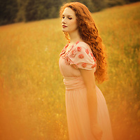 Female youth outdoors in spring wearing a pale pink gown.