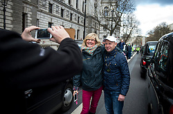 © Licensed to London News Pictures. 10/02/2016. London, UK. A black cab driver poses for a photograph with a tourist as thousands of London black cab drivers stage a protest in Westminster, London against Government interference in the taxi industry and 'active support' for Uber, which they allege is a 'tax avoiding global corporation' Photo credit: Ben Cawthra/LNP