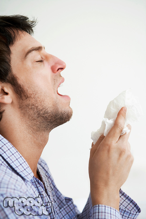 Man about to sneeze into facial tissue