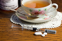 Nightstand displaying various MS medications along with cup of tea. The syringe is a dosage of Rebif. A one month supply of Rebif can cost anywhere from $1,600 to more than $2,000 USD. Rebif is a disease-modifying drug (DMD) used to treat multiple sclerosis in cases of clinically isolated syndromes as well as relapsing forms of multiple sclerosis and is similar to the interferon beta protein produced by the human body. It is co-marketed by EMD Serono and Pfizer in the US under an exception to the Orphan Drug Act. It was approved in Europe in 1998 and in the US in 2002 and is registered in more than 80 countries worldwide. Rebif is administered via subcutaneous injection three times per week, and can be stored at room temperature for up to 30 days.