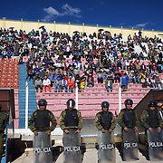 'Attitude at Altitude' Football in Potosi, Bolivia'..Police near the players and officials tunnels during the Bolivia League match between Real Potosi and Wilstermann at the The Estadio Victor Agustin Ugarte, Potosi, Bolivia, Real Potosi won the match 3-0. 2nd May 2010. Photo Tim Clayton..'Attitude at Altitude' Football in Potosi, Bolivia'..The Calvario players greet the final whistle with joyous celebration, high fives and bear hugs the players are sprayed with local Potosina beer after a monumental 3-1 victory over arch rivals Galpes S.C. in the Liga Deportiva San Cristobal. The Cup Final, high in the hills over Potosi. Bolivia, is a scene familiar to many small local football leagues around the world, only this time the game isn't played on grass but a rock hard earth pitch amongst gravel and boulders and white lines that are as straight as a witches nose, The hard surface resembles the earth from Cerro Rico the huge mountain that overlooks the town. .. Sitting at 4,090M (13,420 Feet) above sea level the small mining community of Potosi, Bolivia is one of the highest cities in the world by elevation and sits 'sky high' in the hills of the land locked nation. ..Overlooking the city is the infamous mountain, Cerro Rico (rich mountain), a mountain conceived to be made of silver ore. It was the major supplier of silver for the spanish empire and has been mined since 1546, according to records 45,000 tons of pure silver were mined from Cerro Rico between 1556 and 1783, 9000 tons of which went to the Spanish Monarchy. The mountain produced fabulous wealth and became one of the largest and wealthiest cities in Latin America. The Extraordinary riches of Potosi were featured in Maguel de Cervantes famous novel 'Don Quixote'. One theory holds that the mint mark of Potosi, the letters PTSI superimposed on one another is the origin of the dollar sign...Today mainly zinc, lead, tin and small quantities of silver are extracted from the mine by over 100 co operatives and privat