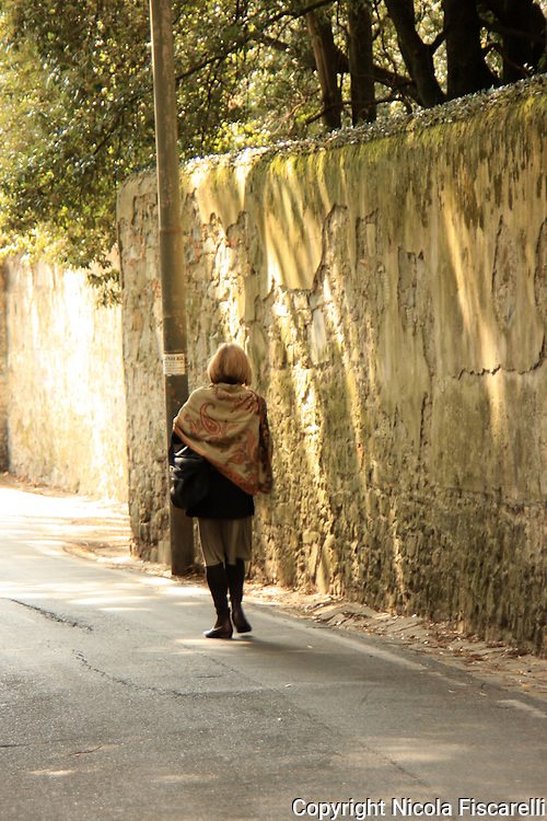An elegantly dressed woman walks on a narrow walled street in Florence.