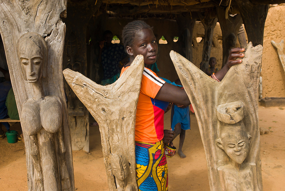 Girl stands by tipical Dogon wood carvings that serve as pillars for roofs. Dogon sculptures are famous for its spiritual symbolism and rarities some times are sold tourists with no scruples. The Dogon Country is the most visited part of Mali with tourists visiting its tipical  villages that can be located on the cliff, on the sandy plain or in the rocky plateau