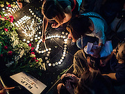 18 AUGUST 2015 - BANGKOK, THAILAND: People light candles in the shape of a heart to honor the deceased at a makeshift memorial in front of Erawan Shrine, which was damaged by a bomb Monday night. An explosion at Erawan Shrine, a popular tourist attraction and important religious shrine in the heart of the Bangkok shopping district, killed at least 20 people and injured more than 120 others, including foreign tourists, during the Monday evening rush hour. Twelve of the dead were killed at the scene. Thai police said an Improvised Explosive Device (IED) was detonated at 18.55. Police said the bomb was made of more than six pounds of explosives stuffed in a pipe and wrapped with white cloth. Its destructive radius was estimated at 100 meters.     PHOTO BY JACK KURTZ