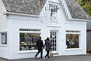 Couple walking past Fisherman's Daughter clapboard store and window shopping, in High Street at Chatham, Cape Cod New England, USA