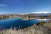 across the azure blue of lake dunstan, sits cromwell amidst the blue sky and mountains of the otago region, new zealand