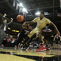 UCF Knights guard Brandon Goodwin (22) gets tripped up by Louisville Cardinals forward Akoy Agau (22) as Louisville head coach Rick Pitono throws his arms up in frustration during an NCAA basketball game between the 14th ranked Louisville Cardinals and the UCF Knights at the CFE Arena on Tuesday, December 31, 2013 in Orlando, Florida. (AP Photo/Alex Menendez)