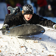 A boy sledding in Central Park after New York City was hit with over 7 inches of snow during its first winter storm of the year. Central Park, Manhattan, New York, USA. 4th January 2014 Photo Tim Clayton