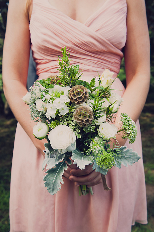 Detail shot of bridesmaid holding bouquet in pastel pink dress
