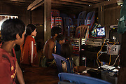 Children watch a movie on a laptop powered by a car battery. Most of Cambodians lack electricity and car batteries, which are charged once a week by a fuel-powered machine, are commonly used to power up small electronic devices or light bulbs. <br /> Most of the hydroelectric projects planned along the Mekong river seem to be necessary for the power demand from the rising metropolis around south-east asia. The LSS2 dam could potentially generate a fifth of the power Cambodia is likely to need by 2018 but the effects on the environment are devastating.<br /> Kbal Romeas, Stung Treng, northern Cambodia.