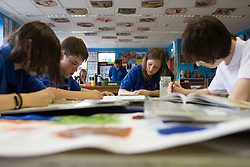 Group of students painting and drawing working towards a final piece in the Art class,