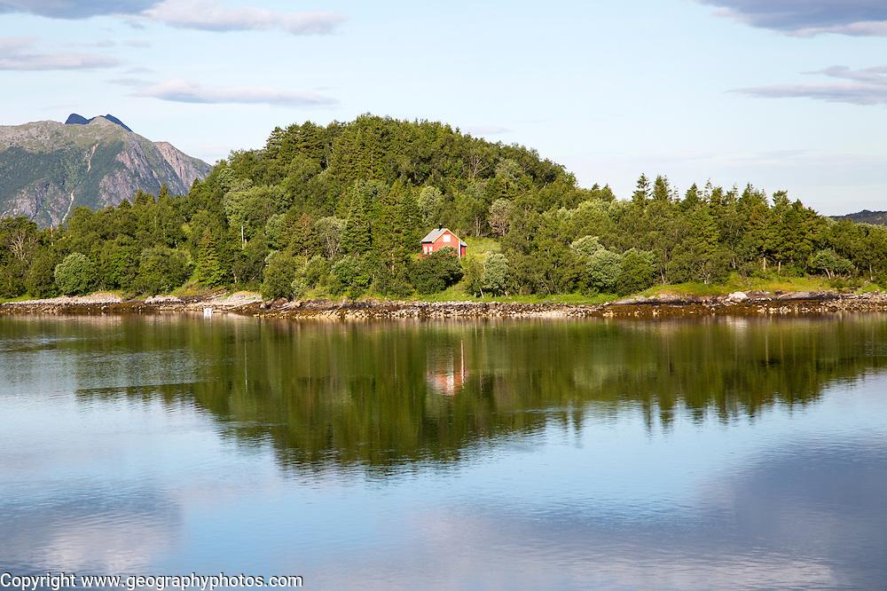 Isolated coastal house on small wooded island near Ornes, Nordland, Norway