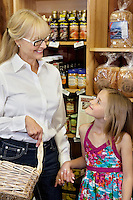 Happy woman with granddaughter holding hands while looking at each other in market