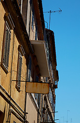 Building with window shutters against cloudless blue sky