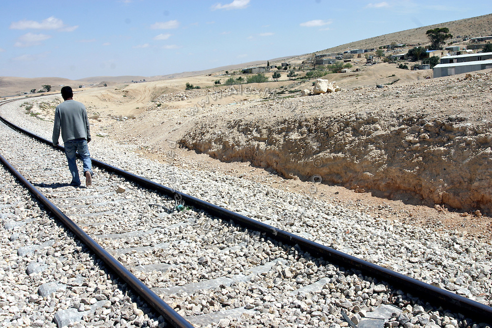 A young Bedouin man is walking barefoot on the railway passing close to his village, the unrecognised settlement of Gasar Al Sar. Numbering around 200.000 in Israel, the Bedouins constitute the native ethnic group of these areas, they farm, grow wheat, olives and live in complete self sufficiency. Many of them were in these lands long before the Israeli State was created and their traditional lifestyle is now threatened by subtle Governmental policies. The seven Bedouin towns already built are all between the 10 more impoverished towns in Israel.