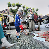 Nederland, Broek in Waterland, 9 juni 2011..reizende poeziegezelschap treedt op en draagt voor op het Kerkplein in Broek in Waterland.Poetry performers on music.