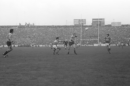 Dublin palms the ball away as he is tackled by Kerry during the All Ireland Senior Gaelic Football Final, Kerry v Dublin in Croke Park on the 28th September 1975. Kerry 2-12 Dublin 0-11.