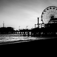 Santa Monica Pier black and white picture. Santa Monica Pier is a landmark located in Los Angeles county that has an amusement park with a ferris wheel, roller coaster, restaurants, and other attractions.