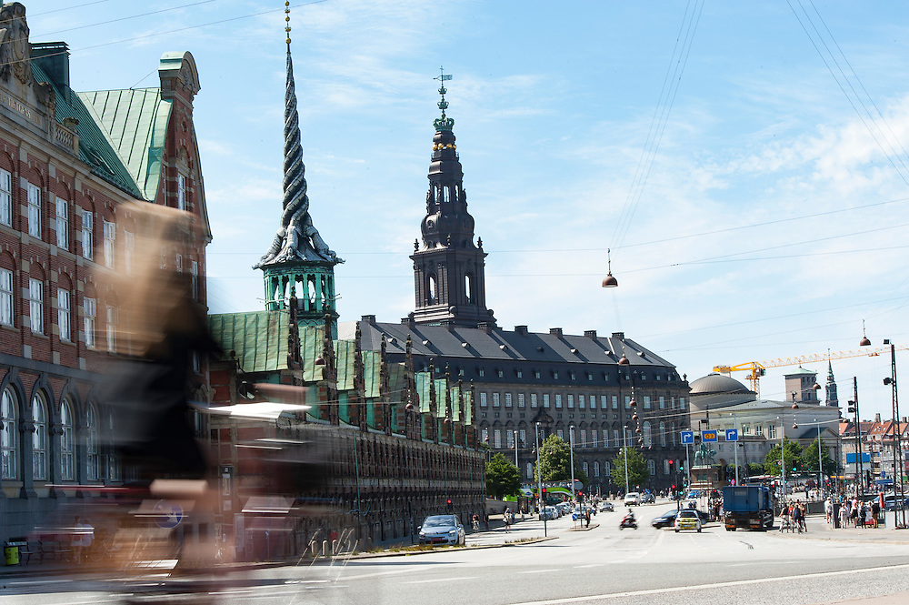 A cyclist zooms past towards Copenhagen's historical Børsen building. An imposing, 17th-century, waterfront building & former stock exchange with a striking spire.