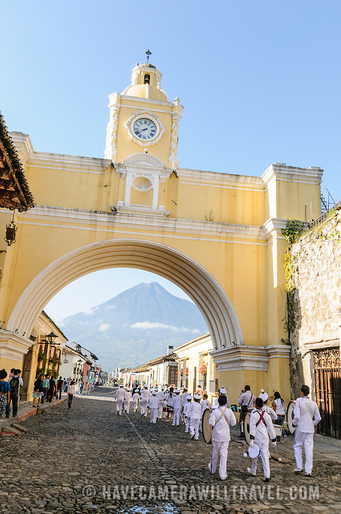 A marching band goes under the arhe at the Santa Catalina in Antigua, Guatemala.