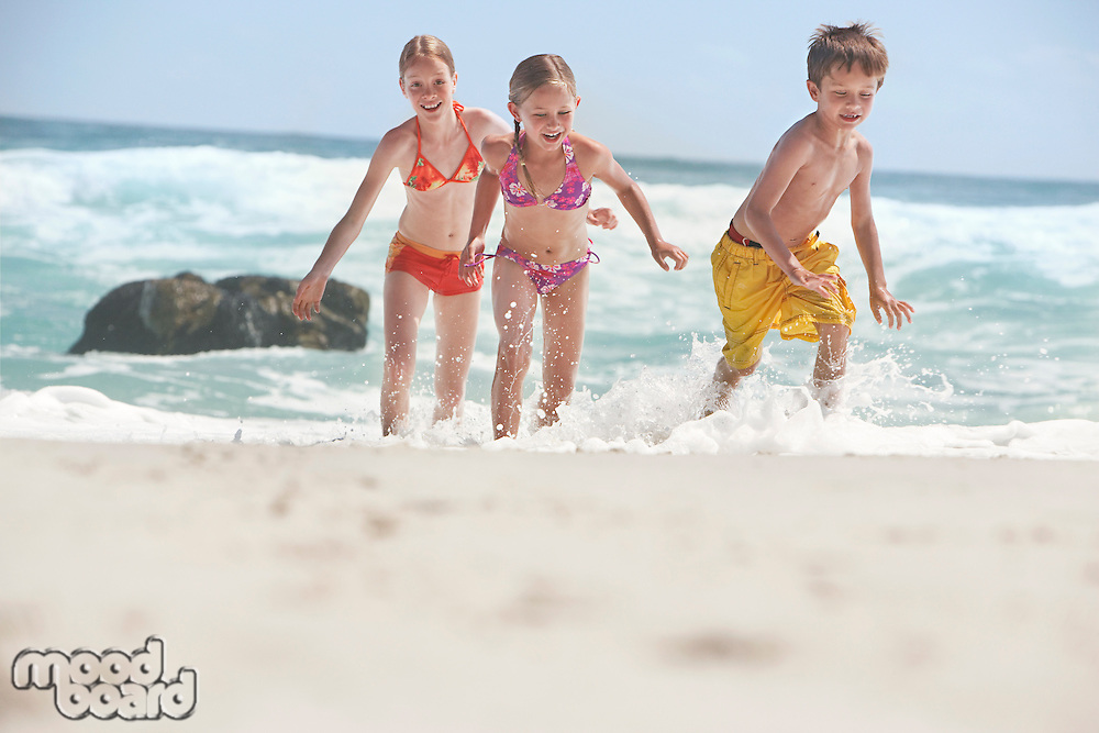 Three children (5-6 7-9 10-12) running on beach