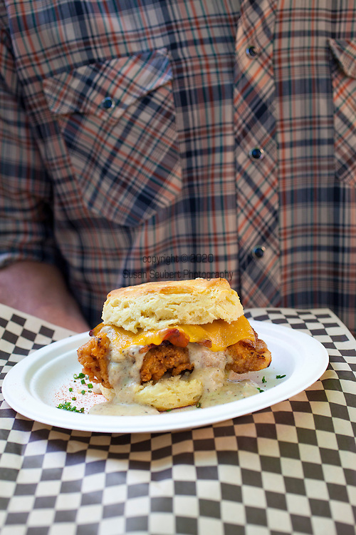 """Pine State Biscuits in Portland, OR at the Saturday Farmers' Market in the South Park Blocks in Portland State University's Campus.  Pictured is Brian Snyder, one of three of the owners.  Brian holding the """"Reggie Deluxe"""" - a buttermilk biscuit with fried chicken, Tillamook cheddar cheese, bacon, a fried egg, all toopped with home made gravy."""