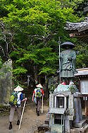 The persons are walking the Shikoku Pilgrimage, by the number 11 temple, Fujii-dera (藤井寺), at the Shikoku Pilgrimage, 88 temples associated with the Buddhist monk Kūkai (Kōbō Daishi, shown in form of a statue in the image) on the island of Shikoku, Tokushima Prefecture, Japan.