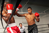 Boxers fighting in ring with referee watching