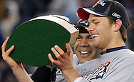 Junior Seau and Tom Brady laugh as they notice their reflections in the AFC Championship Trophy.