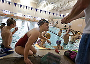 Lehi High School swimmer Amy Chapman gets her interval timer from coach Chad Reimschussel during practice at the Lehi Legacy Center, Tuesday, Dec. 18, 2012. Chapman, 17, was born with fibular hemimelia and had both legs amputated when she was 13 months old. Amy Chapman's Lehi High teammates were uneasy when she first joined the swim team this year but have learned to appreciate her positive attitude.