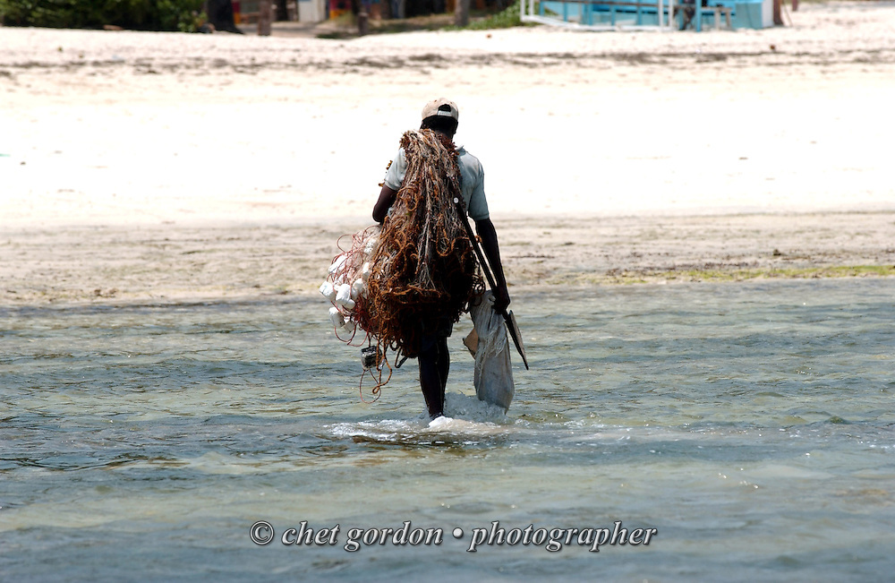 A fisherman walks in the surf as he returns to shore with his netting at Bamburi Beach in Mombasa, Kenya on Friday, February 6, 2004.