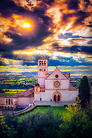 """""""The sun sets like fire in the sky above the Papal Basilica of St. Francis of Assisi""""...<br /> <br /> The seventh morning of our Pilgrimage, we sorrowfully said goodbye to the majestic Sorrento and set out to find the spiritual mecca of Assisi. The excitement of Saint Francis' tiny mountaintop walled village perked our eyes toward the bus windows. Hotel Giotto welcomed all!  An evening Mass with Fr. Peek in the PAX Chapel (a small underground sanctuary in Saint Francis Basilica) hosted our celebration. Mass was celebrated in honor of the wedding anniversary of Bill and Bardeen Dunphy from Atlanta, GA. I cannot say enough about the wonderful quality of people and Catholics in which I had the honor to accompany on our Pilgrimage. A small group of only 12, but mighty in character, affection, spirituality, and compassion. Bill and Bardeen epitomized this nature and shared their love will all our Pilgrims and those who witnessed our gatherings. We were also blessed by a humble, yet charismatic Priest, Father Kevin Peek. He seemed to know every other person in Italy, and subsequently, we all found new friends at dinner time. I cannot honestly conclude a more perfect Pilgrimage Priest than Father, and he was the epitome of a Spiritual guide. He not only celebrated Mass each morning in the most beautiful and prestigious Basilica's in the world, he also led nighttime rosary walks through the Italian Strada, offered confession, interjected stories of the Saints, discussed all Italian epicurean delights with great enthusiasm, and spread the word and love of God to anyone who would listen.  After Mass, the sun once again glowed as it set behind Saint Francis Basilica. There is probably not a more exteriorly photographed church in the world, and it always seems eager to please. The Basilica poses graciously night or day and proudly extends a loving welcome not only to those who are blessed to be there but all those who witness its image created by God and the fortunate artist of"""