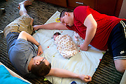 "Jason Holling, left, and Justin Karas, right, take a nap with Abby, center, on August 31, 2014 at their hotel in Illinois. ""You've got to experience the whole thing from birth all the way through school and everything else,"" Holling said. "" I think holding her for the first time in your arms and the first bath and all those type of things its just surreal."""