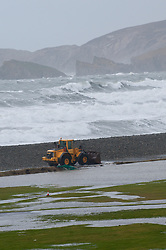 © Licensed to London News Pictures. 05/02/2014. Newgale, Wales. UK. Workmen clear pebbles that have been thrown onto the road behind Newgale beach. Gale force winds and huge waves hit the South & South West Wales coastline ahead of a more serious storm forecast for this weekend. The Met Office said that yet another rapidly deepening area of low pressure will approach the southwest later on Friday bringing heavy downpours with 20-30mm of rain expected within warning areas and 40-50mm possible on high ground in the South West.. Photo credit : Graham M. Lawrence/LNP