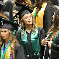 A Member of the Mooreville High School graduating class of 2019 looks for her family in the stands at the BancorpSouth Arena during her their graduation ceremony on Saturday.