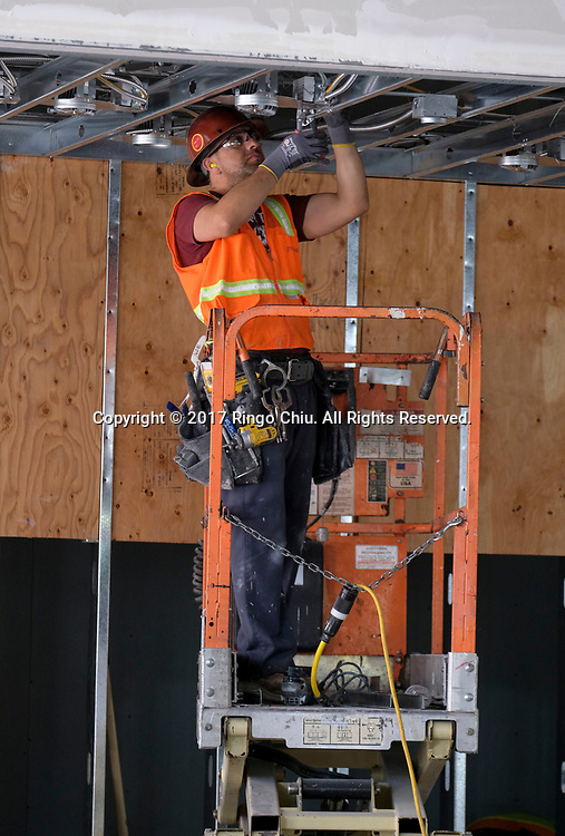 Workers in USC's University Village. USC's $700 million shopping and residential complex is nearly complete and more than a dozen retailers (Trader Joe's, Target, Starbucks, etc.) are set to open in August.(Photo by Ringo Chiu)<br /> <br /> Usage Notes: This content is intended for editorial use only. For other uses, additional clearances may be required.