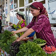 Woman laying out vegetables in market stall, Istaravshan, Tajikistan