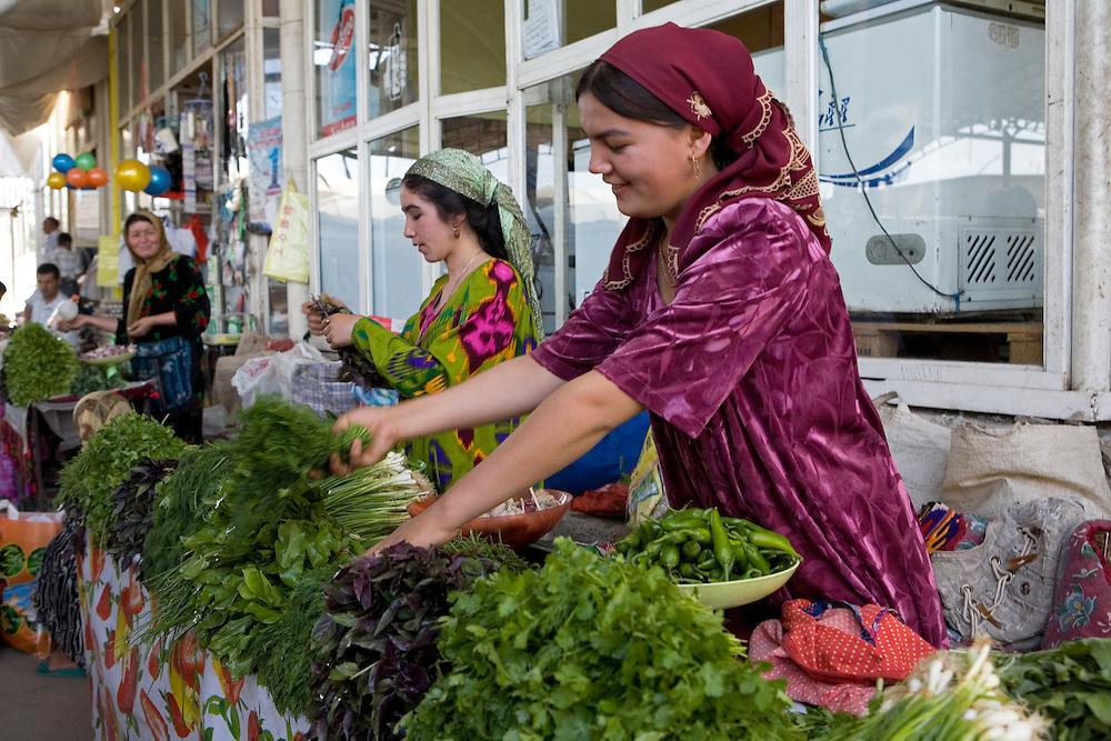 Woman laying out vegetables in market stall, Istaravshan, Tajikistan