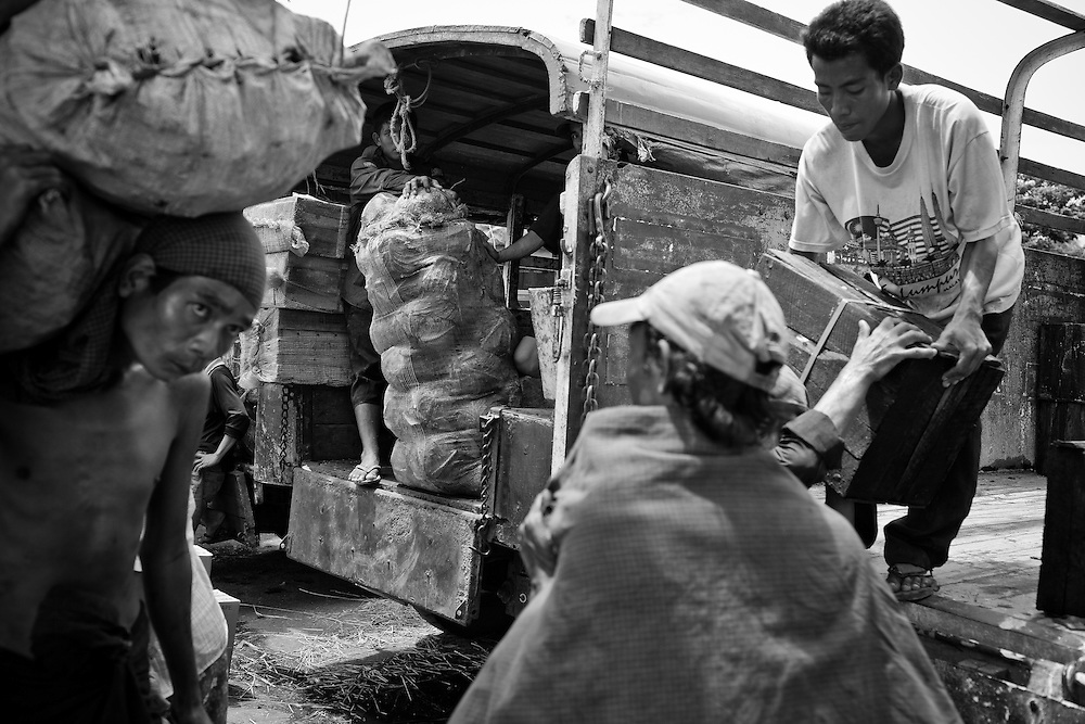 Workers manually unload thousands of sacks of rice and other products from large ships on the docks of Yangon, Myanmar.