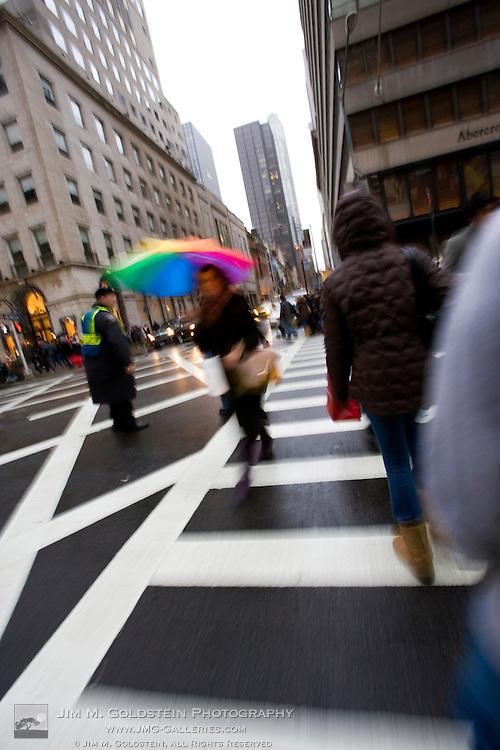 A pedestrian in New York crosses 5th avenue in the rain with a rainbow umbrella