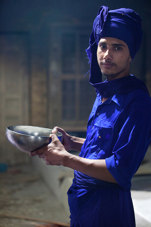 A young Nihang Sikh drinking from his traditional bowl. The Nihangs are warrior sikhs and their attire consists of blue color.