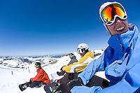 Young woman smiling at camera while snowboarding at Kirkwood resort near Lake Tahoe, CA.<br />