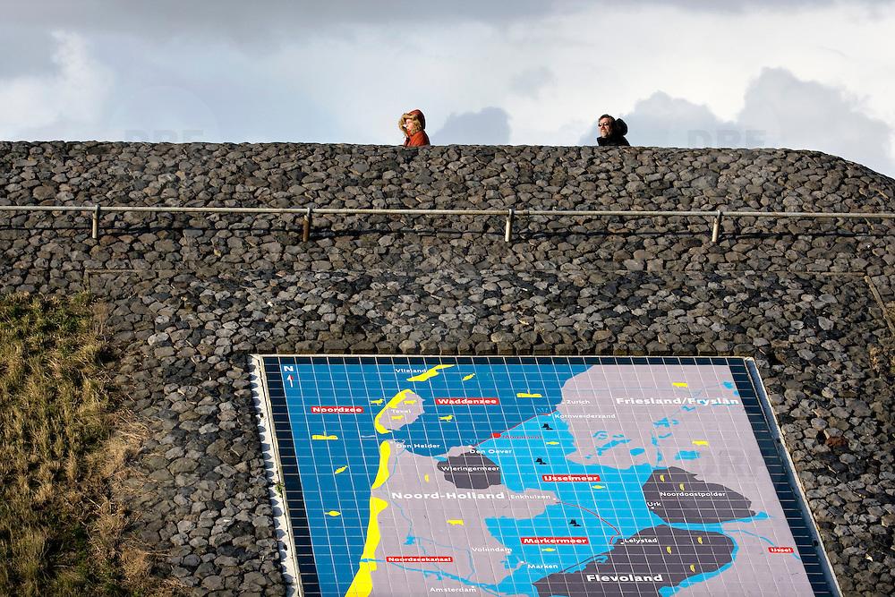 Nederland Den Oever Zurich 22 november 2008 20081122 Foto: David Rozing ..Serie afsluitdijk. De Afsluitdijk is een belangrijke waterkering en verkeersweg in Nederland. De waterkering sluit het IJsselmeer af van de Waddenzee. Hieraan ontleent de dijk zijn naam. De verkeersweg, onderdeel van Rijksweg a7, verbindt Noord-Holland met Friesland....Informatie plaquette / landkaart van gebied rondom afsluitdijk in de afsluitdijk ter hoogte van de uitkijktoren. Bezoekers uitkijkpunt, man, vrouw, guur weer, wind, koud, capuchon,  deltaplan..Foto David Rozing