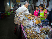 23 SEPTEMBER 2014 - BANGKOK, THAILAND: A man buys meatless snacks from a vendor on the first day of the Vegetarian Festival at the Chit Sia Ma Chinese shrine in Bangkok. The Vegetarian Festival is celebrated throughout Thailand. It is the Thai version of the The Nine Emperor Gods Festival, a nine-day Taoist celebration beginning on the eve of 9th lunar month of the Chinese calendar. During a period of nine days, those who are participating in the festival dress all in white and abstain from eating meat, poultry, seafood, and dairy products. Vendors and proprietors of restaurants indicate that vegetarian food is for sale by putting a yellow flag out with Thai characters for meatless written on it in red.    PHOTO BY JACK KURTZ