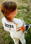 Young girl showing her 4H dairy goat at the county fair, close-up, looking away from camera