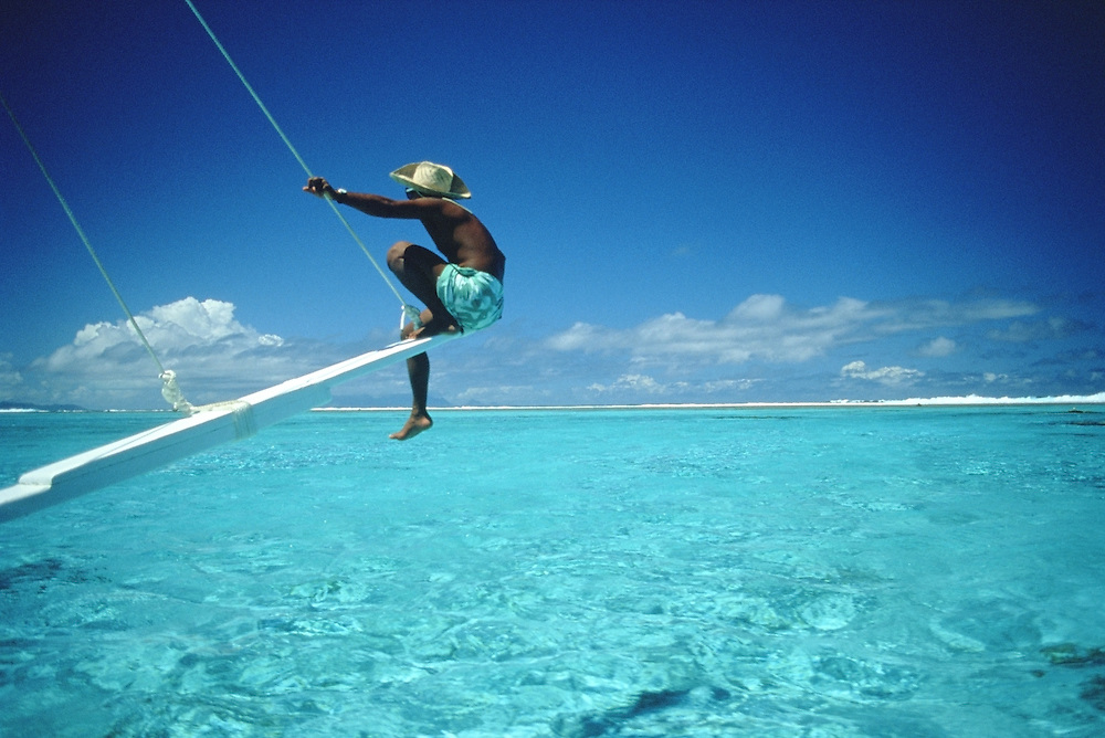 Man out on rail of outrigger in lagoon on the island of Bora Bora, French Polynesia.  Award winning image, Islands magazine Grand Prize.